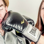 Woman mock-punching man with boxing gloves